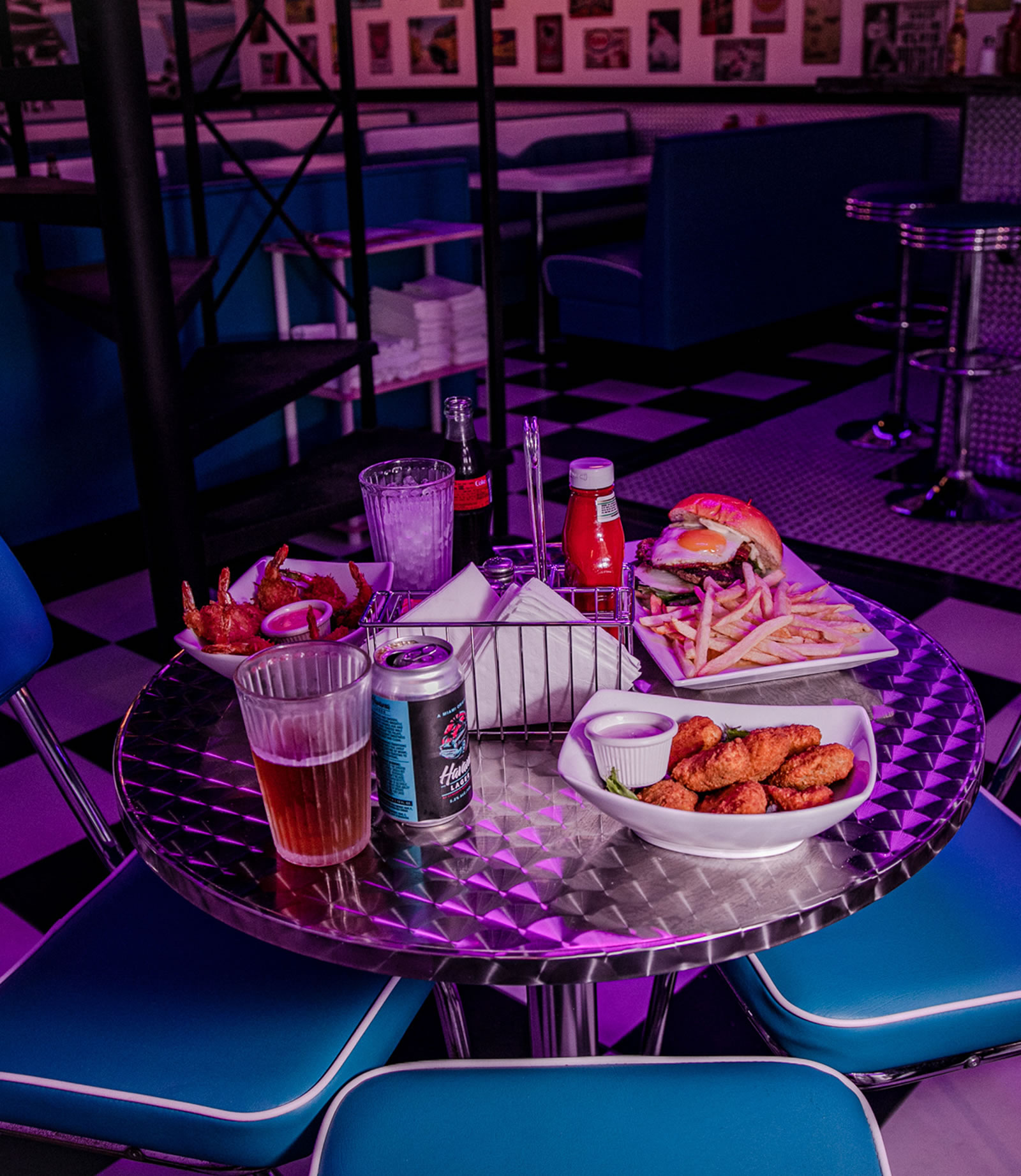 A table served with a dish of nuggets, one hamburger, fried shrimps and a beer.