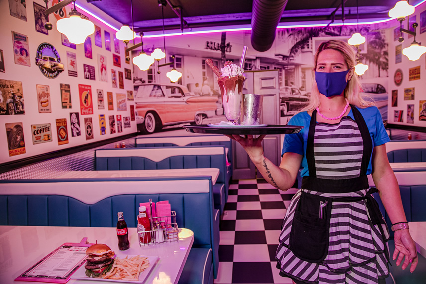 A waitress holding a tray with a milkshake
